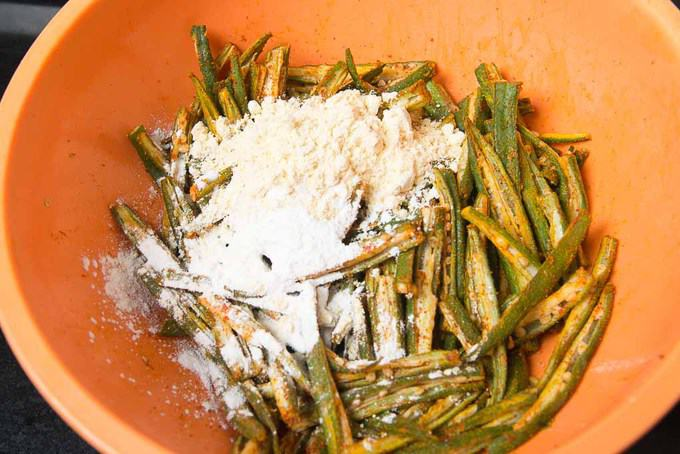 Besan and corn flour added in bhindi in the bowl