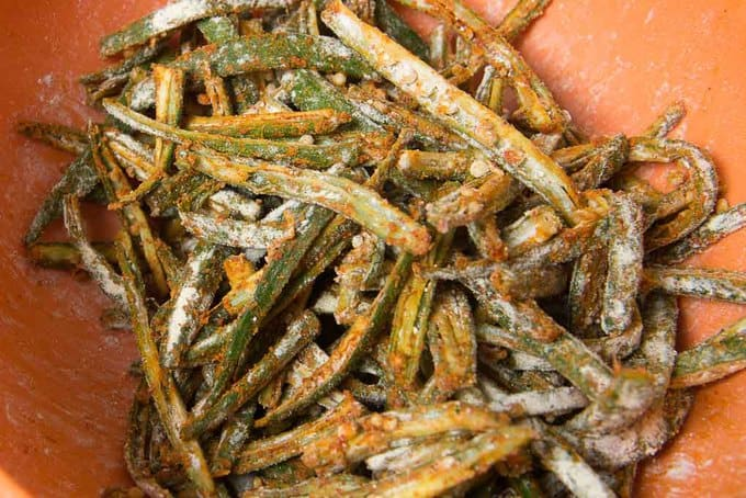 Bhindi mixed with besan and cornflour in a bowl