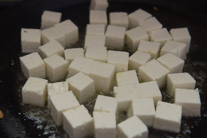 Paneer cubes frying on a pan.