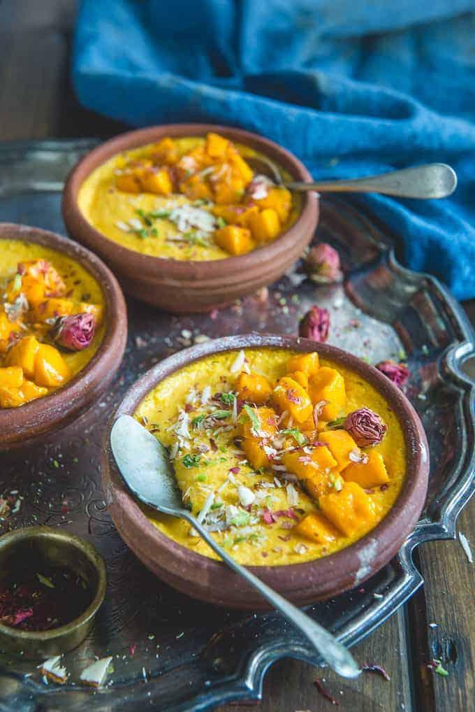 mango phirni served in terracotta bowls.