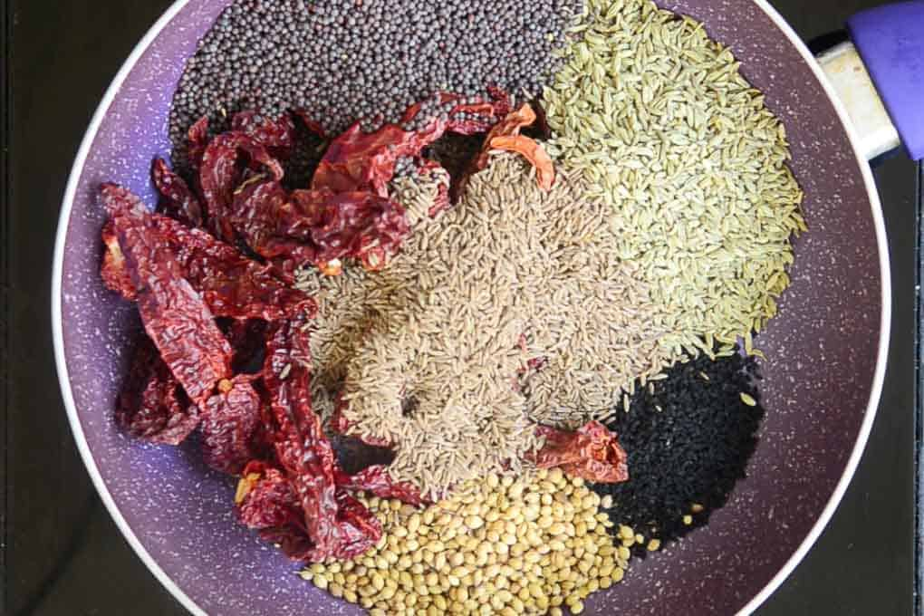 Mustard seeds, dry red chillies, fenugreek seeds, onion seeds, mustard seeds and cumin seeds added in a pan for dry roasting