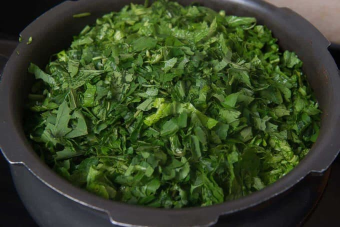 Musrad leaves, bathua, spinach and radish leaves added in a pressure cooker.
