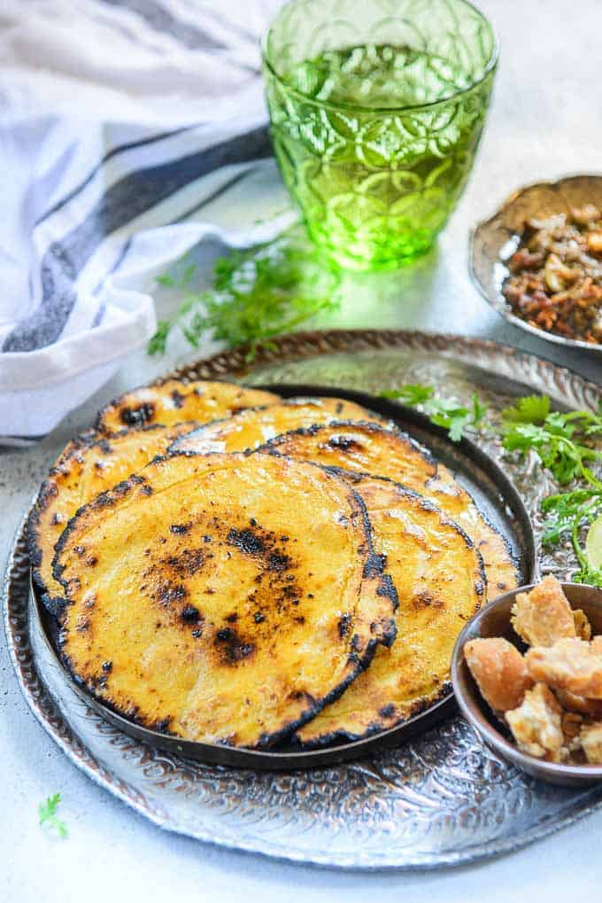 makki ki roti stacked on a plate along with sarson ka saag and jaggery