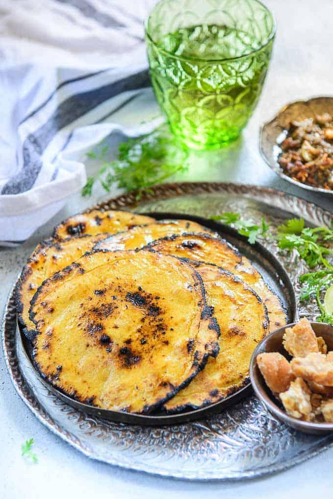 makki ki roti stacked on a plate along with sarson ka saag and jaggery