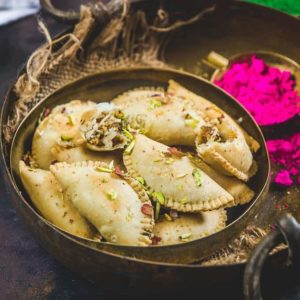 Gujiya is a traditional Indian fried pastry stuffed with coconut and Khoya filling. It is a must make recipe for Holi.