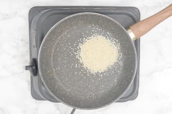 Sesame seeds added in a pan.