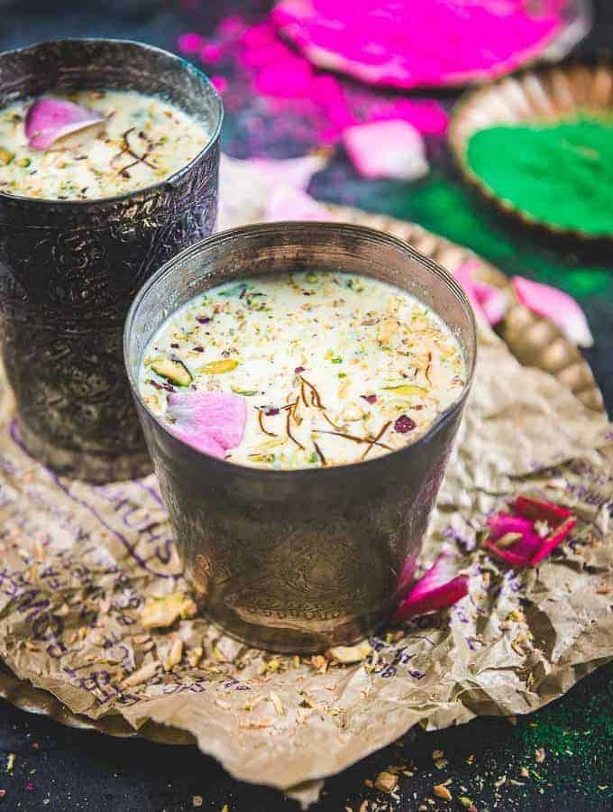 Thandai served in a metal glass garnished with dry fruits and rose petals