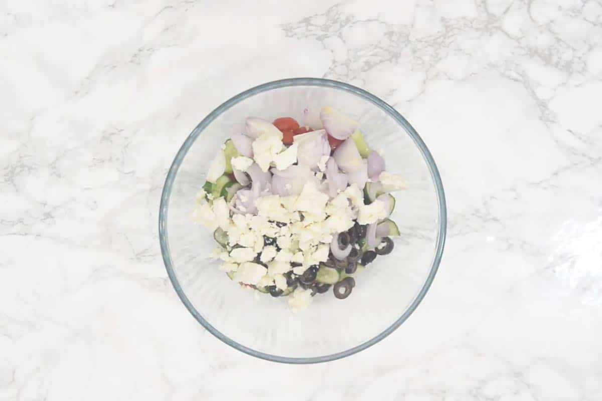 Cherry tomatoes, cucumber, olives and feta cheese mixed in a bowl.