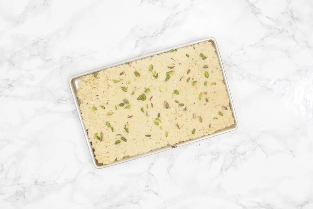 Ready kalakand garnished with pistachio slivers.