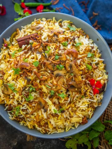 This restaurant style Mushroom Biryani is a homemade dum style veg version of Biryani. Make it at home using my recipe.