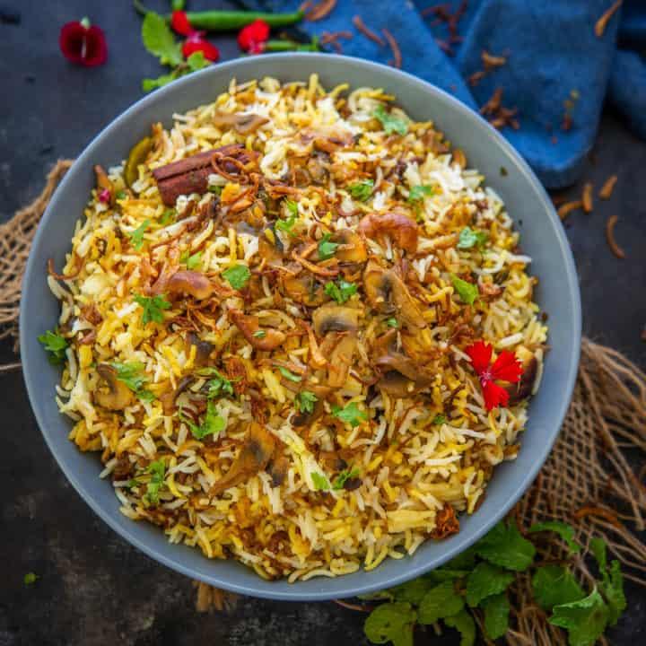 This restaurant style Mushroom Biryani is a homemade dum style veg version of Biryani. Make it at home using my recipe.