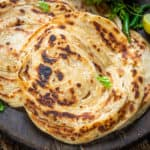 Lachha Paratha is a layered flaky Indian bread which is great to pair with curries. Learn how to make  it at home using my easy recipe.