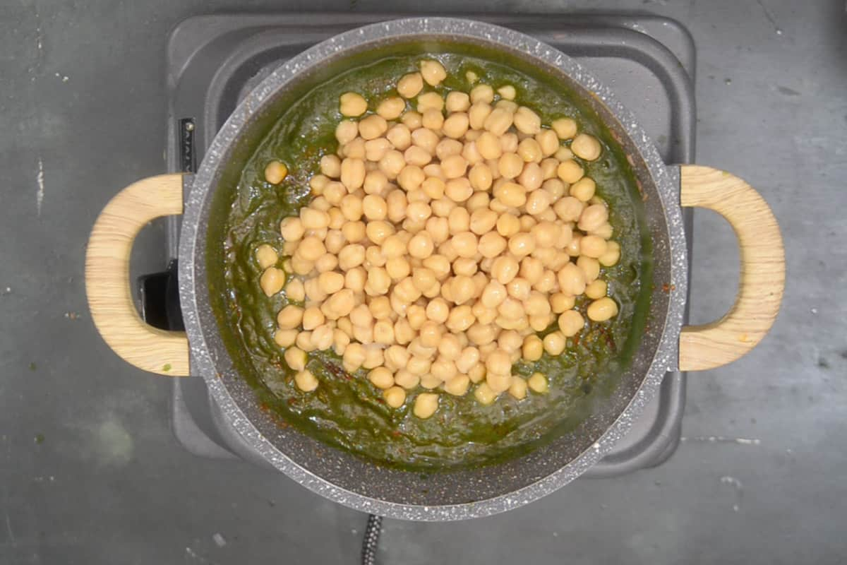Boiled chickepas added in the pan.
