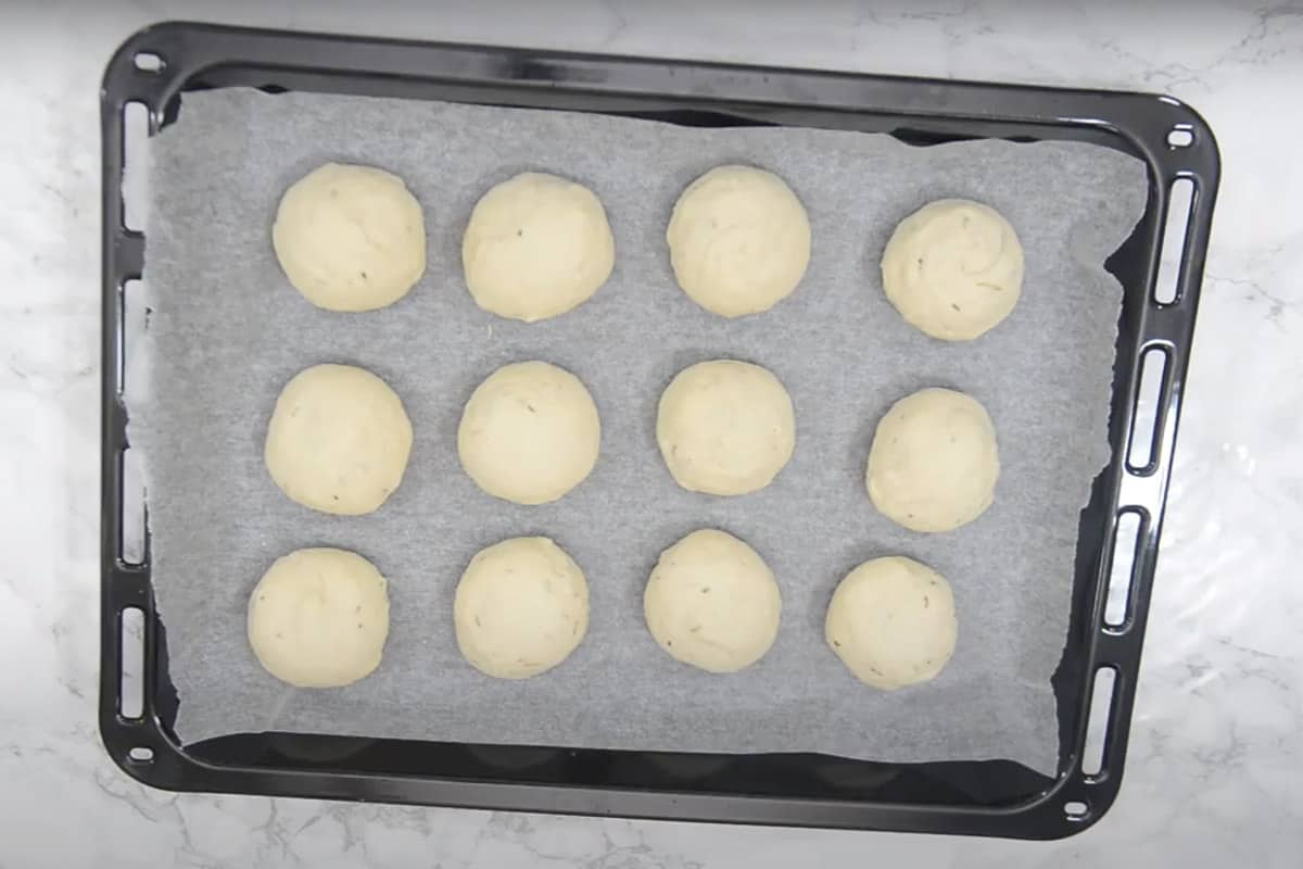 Balls lined on a baking tray lined with parchment.