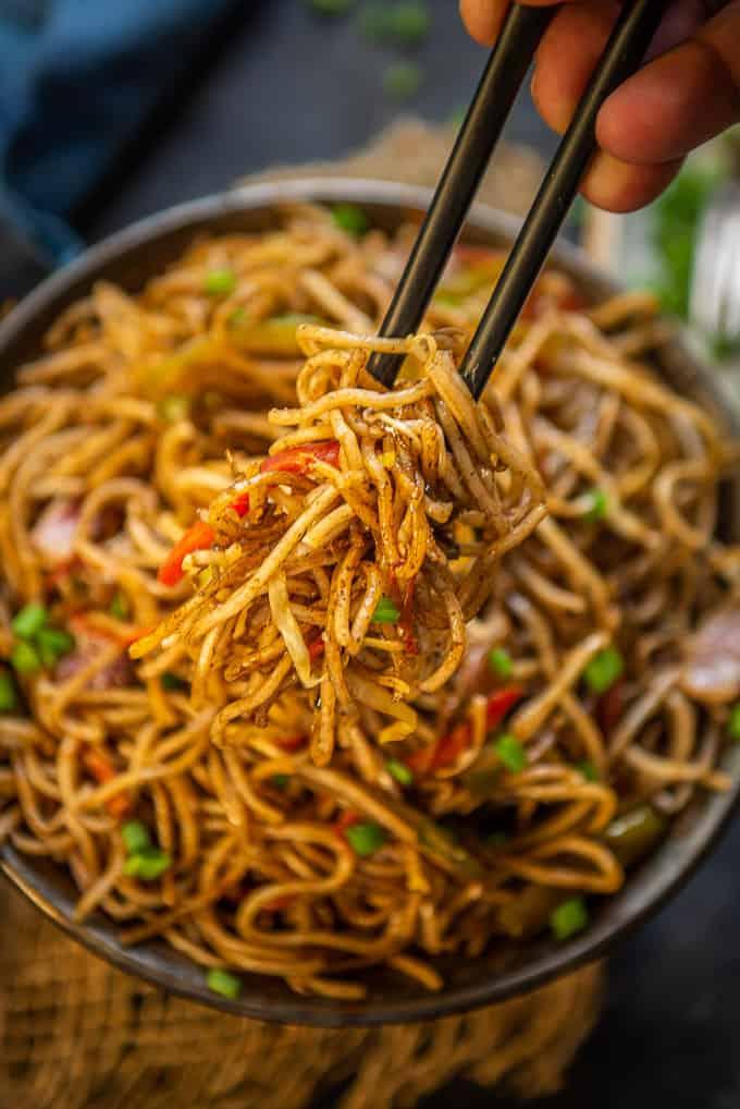 Hakka noodles held by chopsticks.