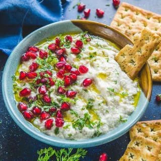 Mutabal served in a serving bowl garnished with coriander, olive oil and pomegranate seeds