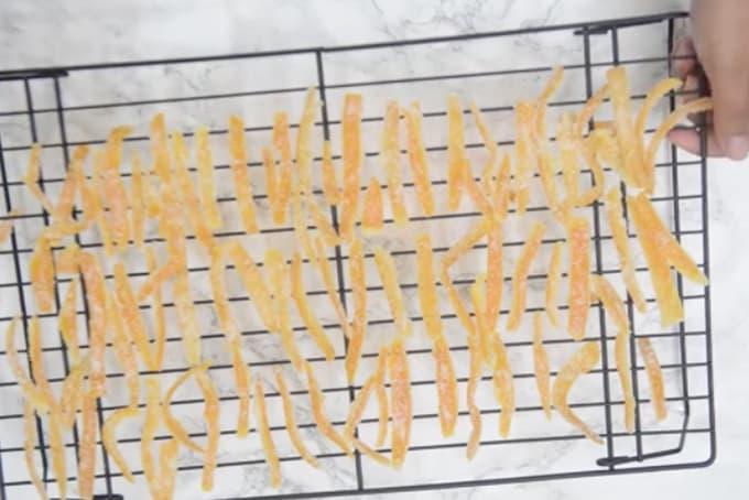 Candied orange peel arranged on a wire rack.