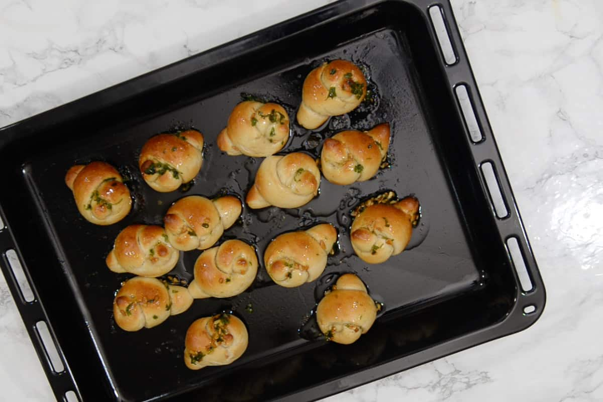 Butter poured over ready garlic knots.