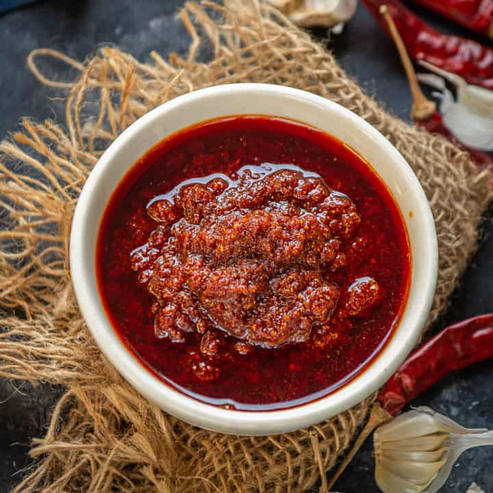 Garlic Chutney is a delicious Rajasthani accompaniment made using lots of garlic and dry red chillies. This fiery red chutney elevates the taste of any Indian meal. Here is how to make it.