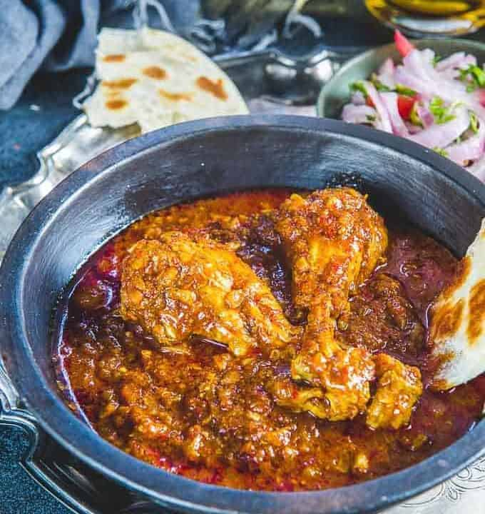 Chicken vindaloo served in a serving bowl along with a bite of paratha