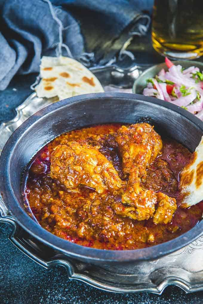 Authentic goan chicken vindaloo goan chicken curry whiskaffair chicken vindaloo served in a serving bowl along with a bite of paratha forumfinder Image collections