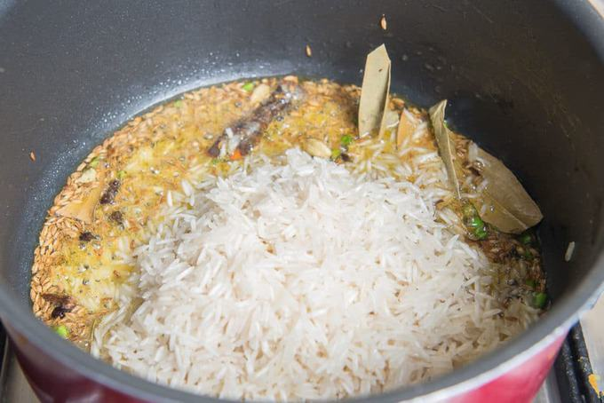 soaked rice, water and bay leaf added in the pan