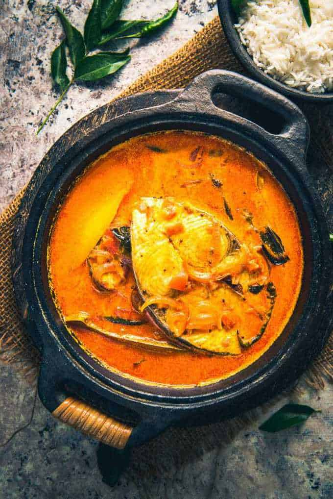 Alleppey Fish Curry served in a serving bowl along with rice.