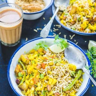 Side view of aloo poha sprinkled with bhujia in a plate along with tea
