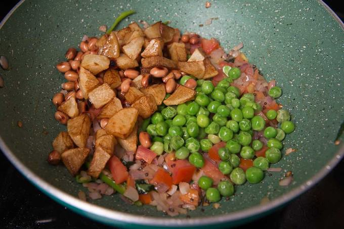 Fried potato, peanuts and green peas added in the pan