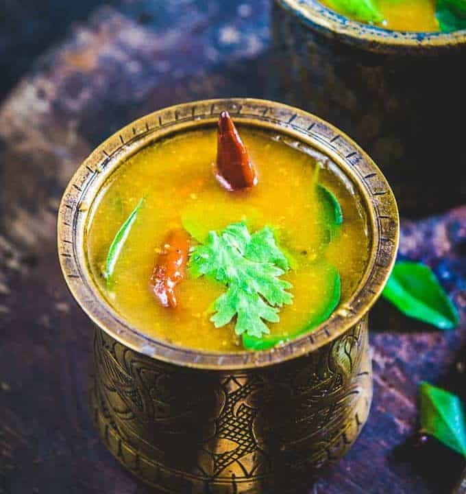 Kerala style rasam served in a bell metal tumbler
