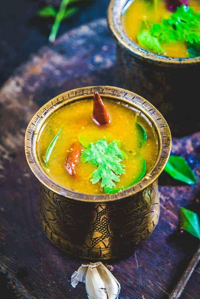 Kerala rasam served in a bell metal tumbler