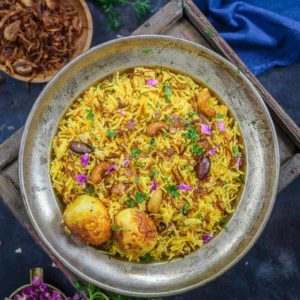 Egg Biryani or Anda Biryani is a flavorful and delicious Indian rice preparation where rice is cooked with a spicy egg layer. It is a take on Hyderabadi Gosht Biryani and is super easy to make at home. Here is how to make egg biryani recipe at home.