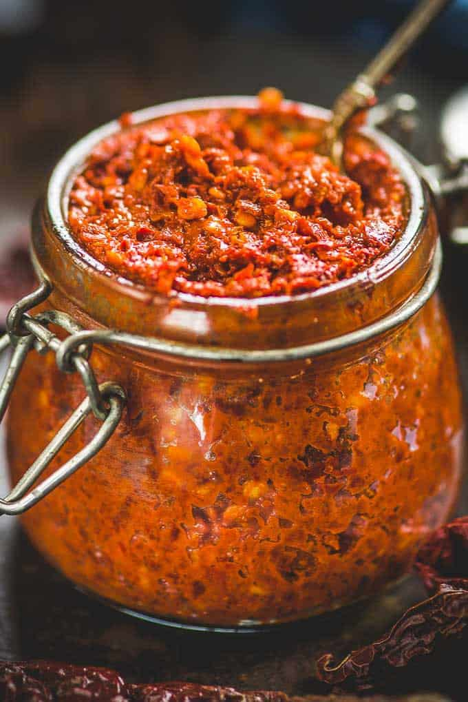 close up view of red chilli paste in the glass jar.