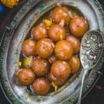 Gulab Jamun are classic Indian dessert which is enjoyed by everyone. These are delectably sweet balls delicately flavored with rose water and dunked in sugar syrup.