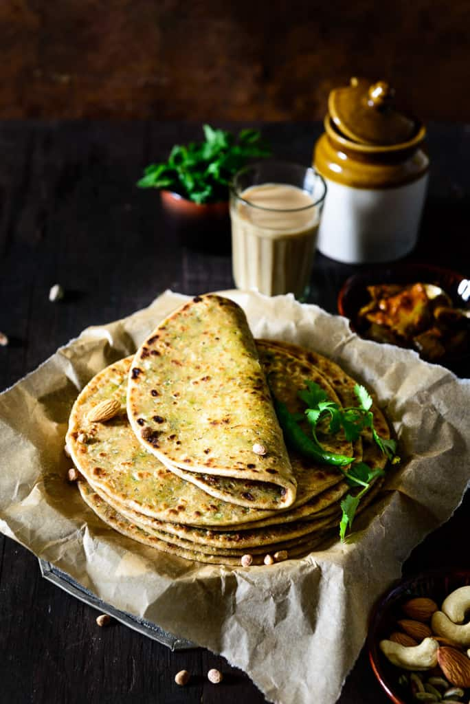 Stack of Dry Fruits Paratha in a tray along with pickle jar and tea