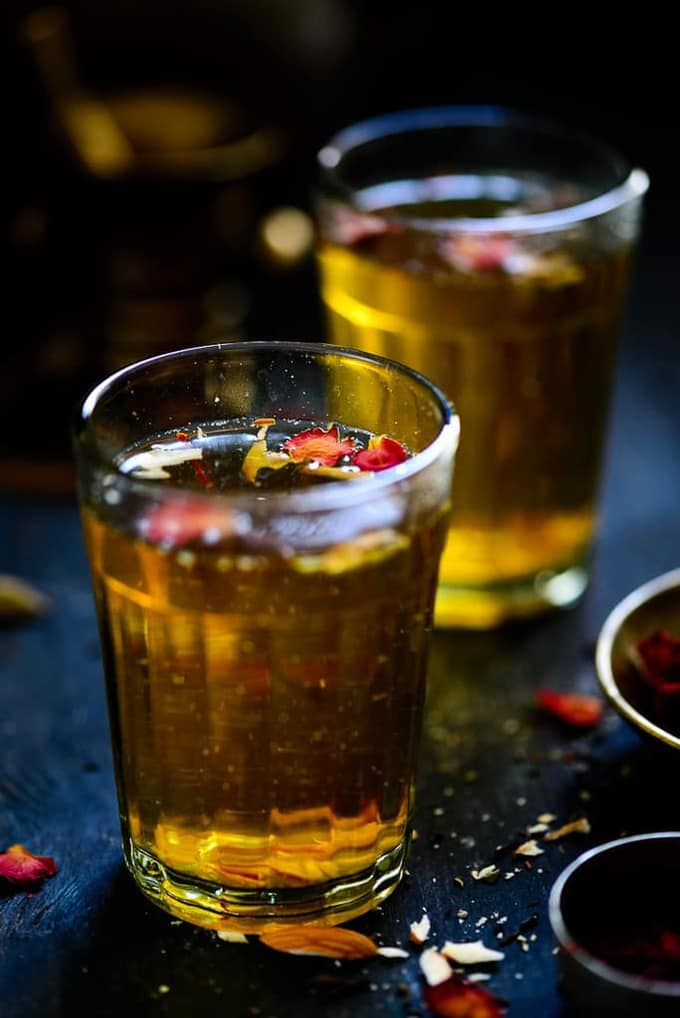 Kashmiri Kahwa served in glasses garnished with rose petals, almond slivers and saffron