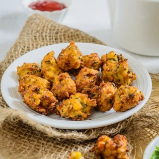 Makai ke Pakode are made with boiled corn and a blend of spices. They are crisp and crunchy on the outside and soft, warm, melt-in-the-mouth on the inside. Besides corn kernels, you can even add onions and other veggies if you choose. What is important is the gram flour that binds everything together.