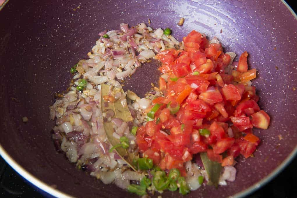 Tomatoes and green chilli added in the pan.