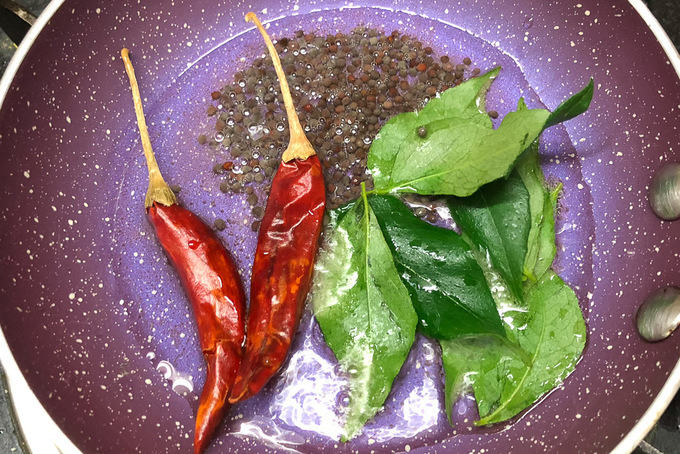 Curry leaves, dry red chillies and musrad seeds added in hot coconut oil.