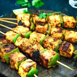 Paneer Tikka served on a wooden platter