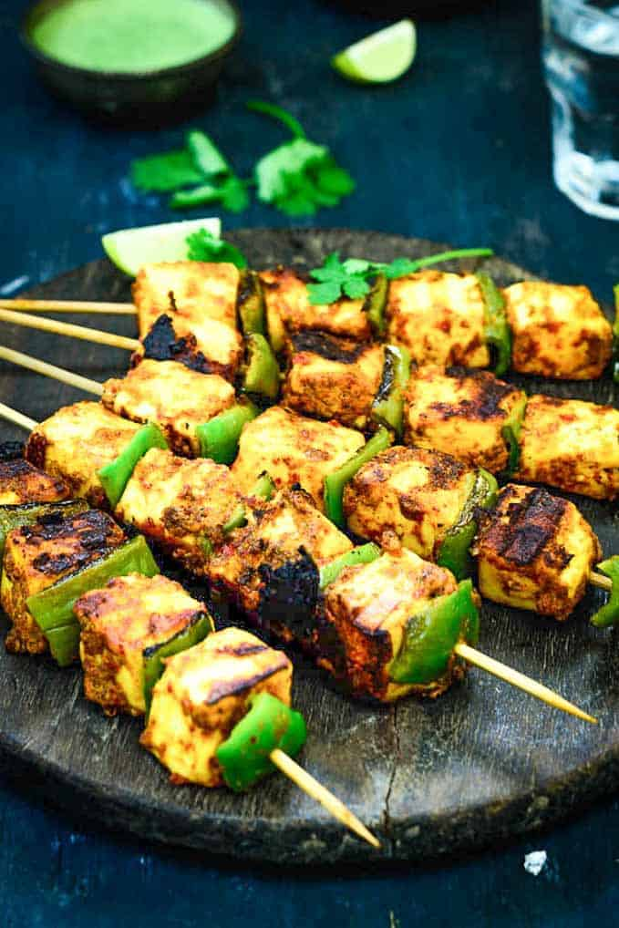 Achari Paneer Tikka served on a wooden platter