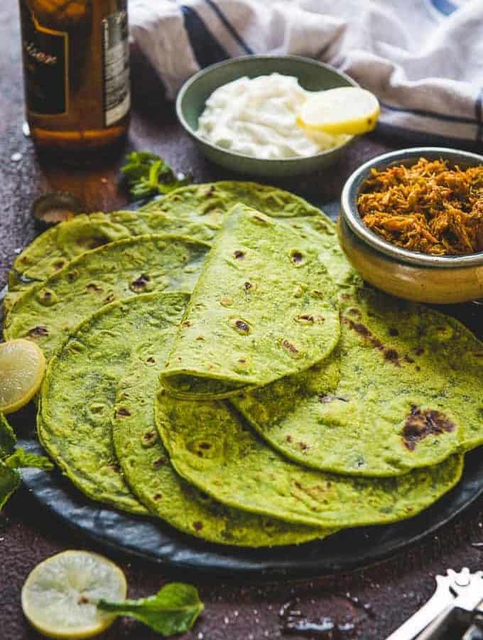 Spinach tortilla served on a plate along with sour cream and pulled chicken