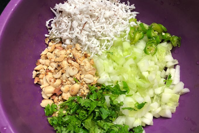Cucumber, coconut, peanut, coriander and chilli mixed in a bowl.