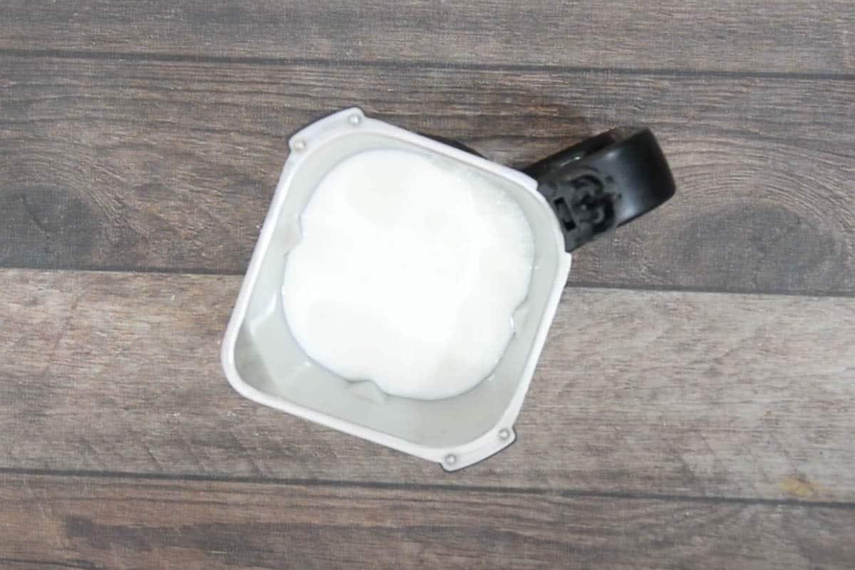 Shrikhand, buttermilk and milk added to a blender.