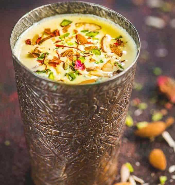 badam milk recipe served in a traditional brass glass