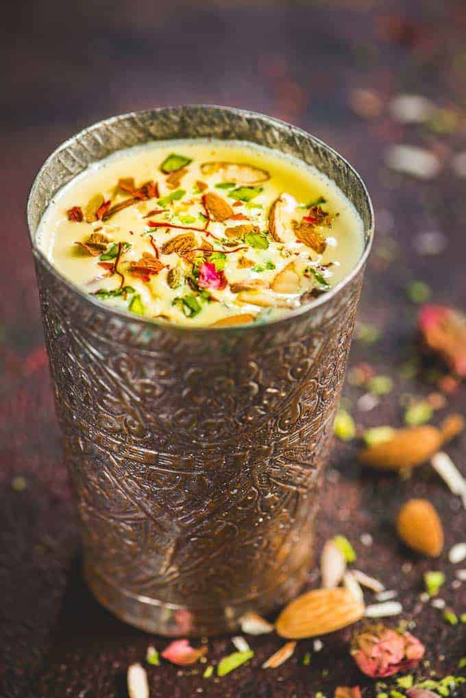 badam milk recipe served in a traditional brass glass