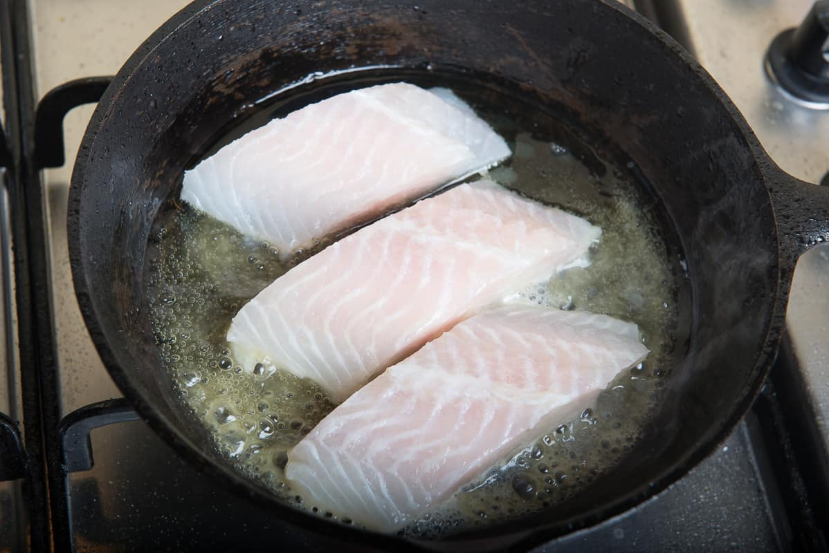 Fish fillets being fried in hot olive oil on an iron skillet