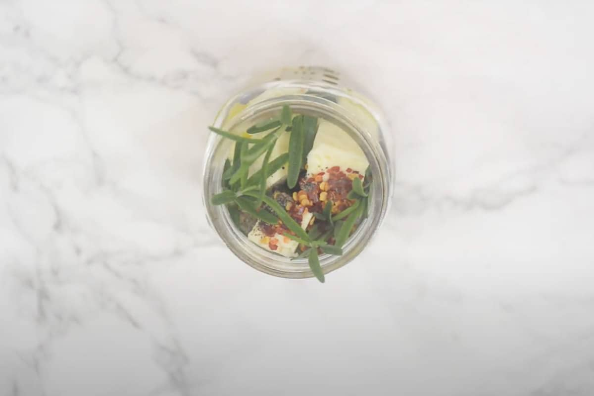 Olive oil, rosemary, red chili flakes, and black pepper added in the jar