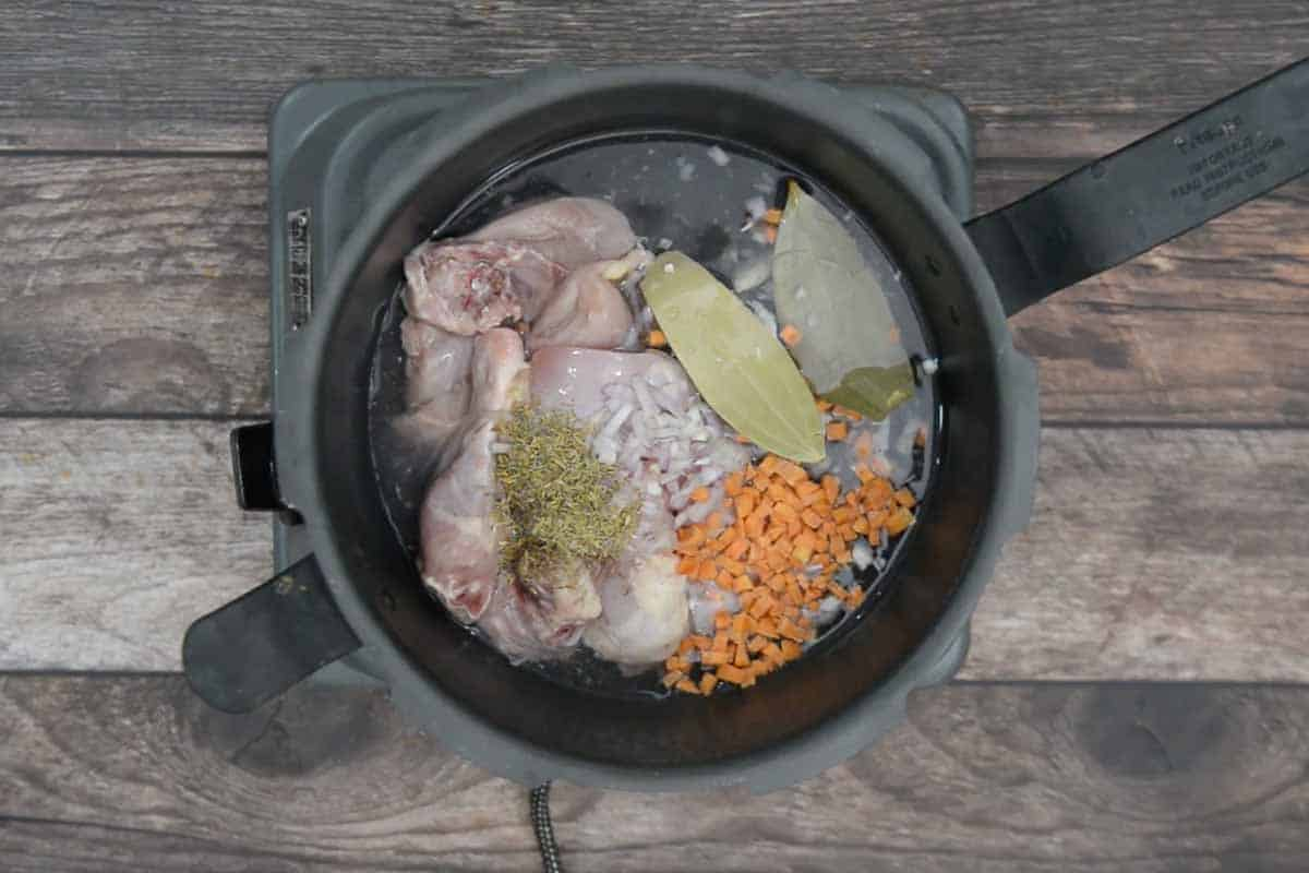 Chicken, onion, garlic, carrot, bay leaf, thyme, and water added to a pressure cooker.