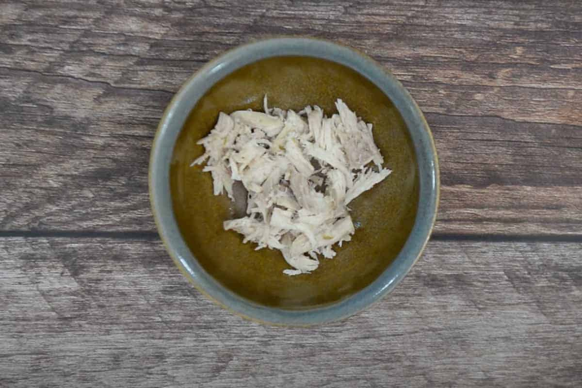 Some shredded chicken added in a serving bowl.